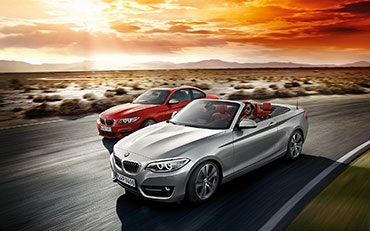 Photograph of a BMW 2 Series car being driven on a road through a desert, driving by a red BMW 2 Series car