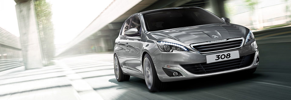 The Peugeot 308 driving down a street.