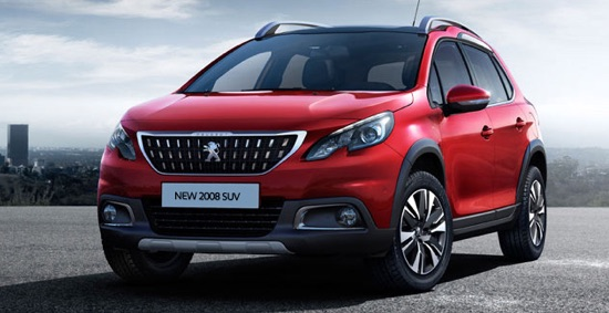 Red Peugeot 2008 parked in the sun with cityscape in background.